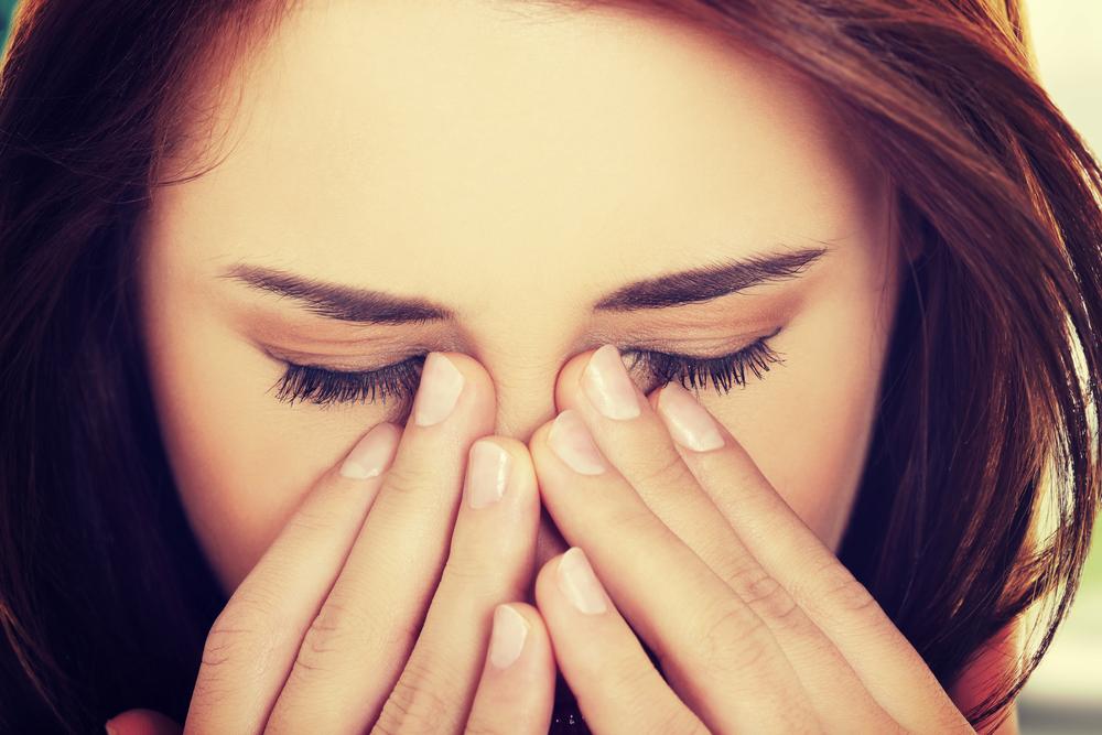 девушка закрыла глаза и пальцами закрывает нос
