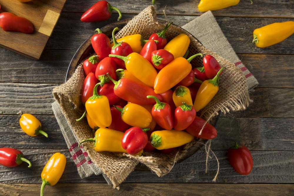 маленькие желтые и красные болгарские перцы на деревянном столе