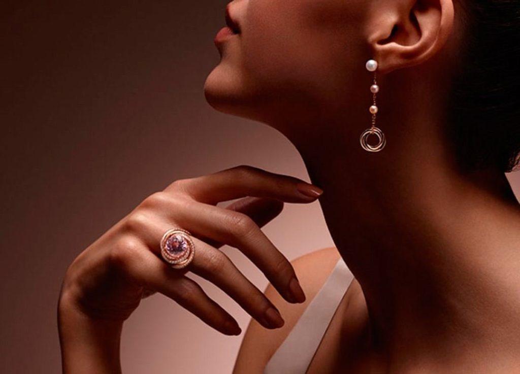 золотая серёжка с жемчугом и кольцо на руке