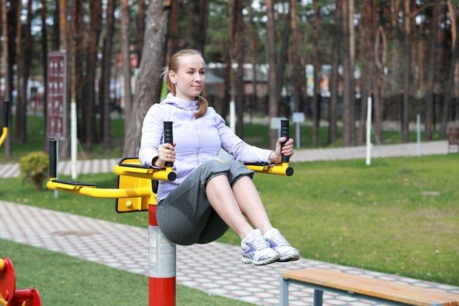 Девушка на уличном тренажере