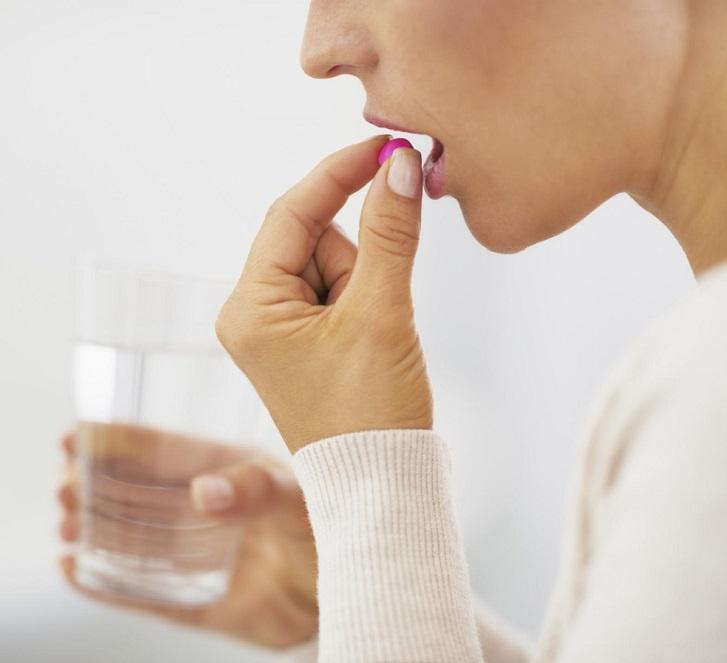 Женщина пьет таблетку для профилактики от глистов