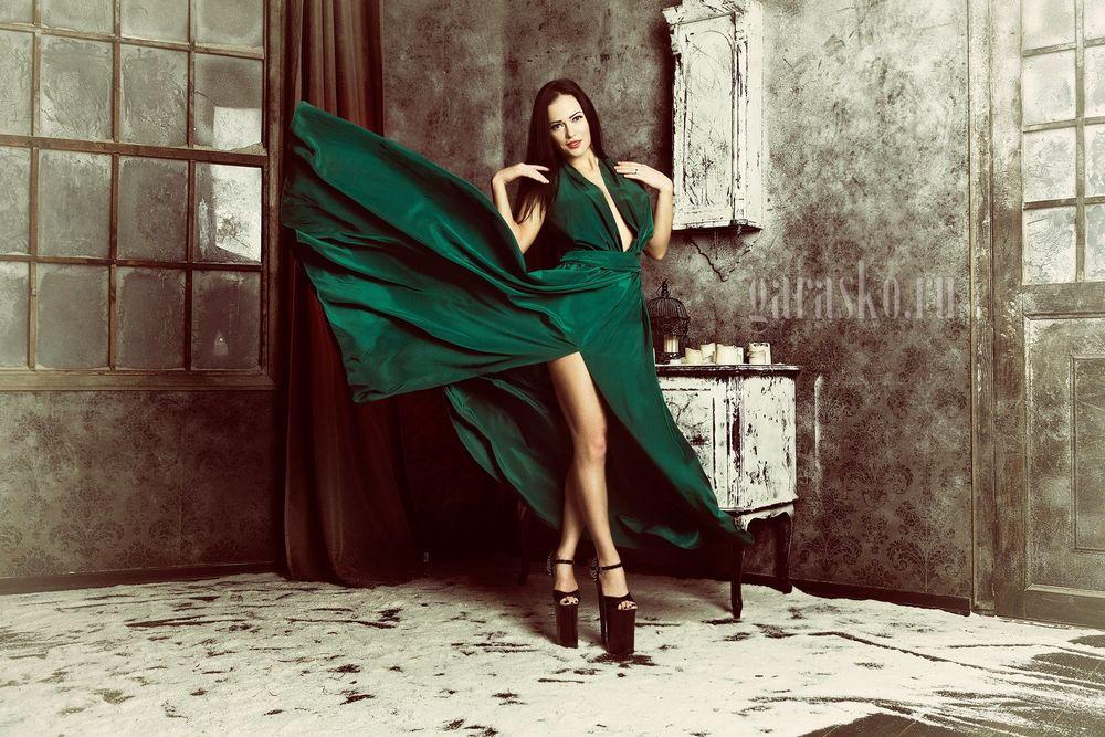 девушка в комнате в изумрудном платье