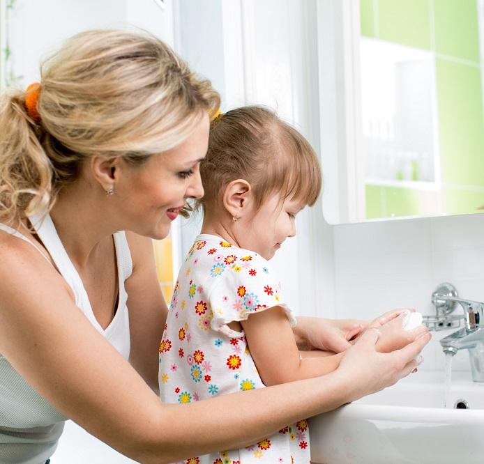Мама моет маленькому руки ребенку во избежание заражения глистами